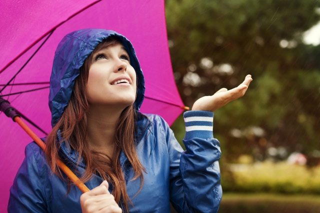 Beautiful young woman in raincoat with umbrella checking for rain